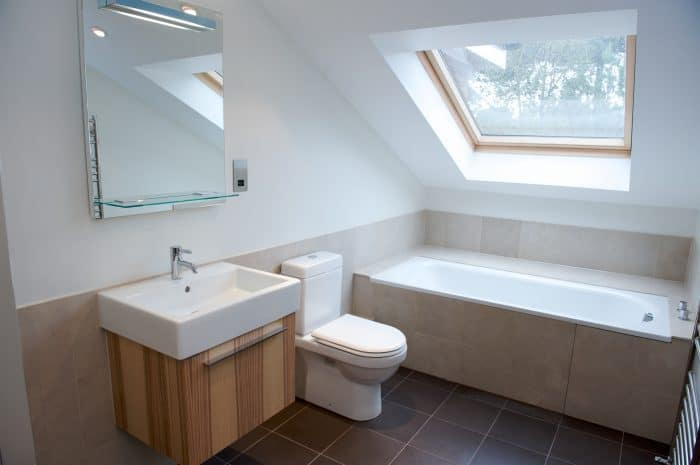 Bathroom Loft conversion built into the eaves of a house with Velux roof windows providing light.
